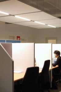 Die akustischen Stellwände separieren die Arbeitsplätze. Die Deckensegel verbinden Akustik und Licht.